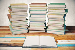 Three piles of books and blank diary in the middle on wooden tab Royalty Free Stock Photo