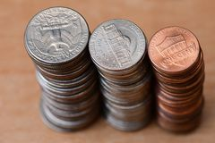 Three piles of coins. Silver quarters, silver nickels and copper pennies in three equal piles of money Stock Images