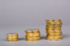 Three piles of gold coins with a graph of growth upward royalty free stock photos