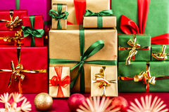 Three Piles of Xmas Gifts in Red, Gold and Green. Three stacks of plain Christmas presents assorted by color. Red, gold and green. Blurred baubles and stars in Stock Photography