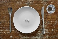 Three pills on plate knife and fork Royalty Free Stock Photo