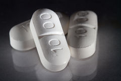 Three pills with reflection Royalty Free Stock Photo