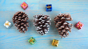 Three Pine cones and gifts around them. Stock Photo