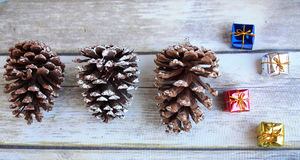 Three Pine cones and gifts Royalty Free Stock Photos