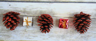 Three Pine cones small reds silver gifts next to them. Stock Photography