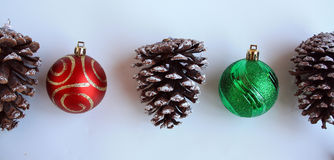 Three Pine cones and two Christmas balls cropped closer Royalty Free Stock Image