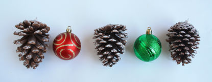 Three Pine cones and two Christmas balls Royalty Free Stock Photo