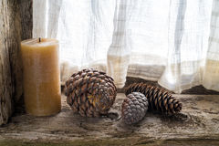 Three pinecones and a candle Royalty Free Stock Photos