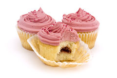 Three pink cupcakes. Three pink cup cakes on a white background with one bite taken Stock Image