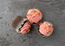 Three pink frosted chocolate cupcakes on a gray background top view royalty free stock images