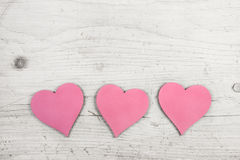 Three pink hearts on old wooden white shabby chic background. Stock Photography