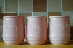 Three pink jugs on a wooden kitchen work surface, with the words. `Tea`, `Coffee` and `Sugar stock images