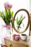 Three pink macaroons and cup of coffee, pink tulips and mirror Stock Photo