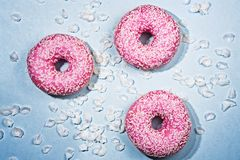 Three pink sparkled doughnouts royalty free stock images
