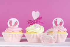 Three pink theme baby girl cupcakes on pink Stock Photo