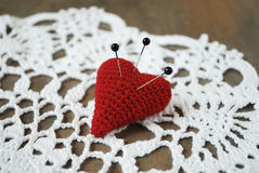 Three pins stuck in crochet heart. Stock Image