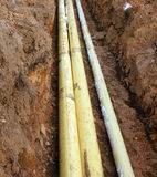 Three pipes in the trench in the ground Stock Image