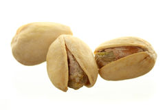Three Pistachios. Three Pistachio Nuts Isolated Against White Ground royalty free stock photography