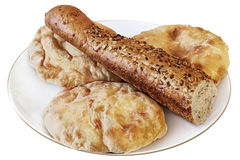 Three Pita Bread Loafs And Integral Baguette Half On White Plate. This photograph represents three pita bread loafs and one half of integral baguette on top, all Stock Photo