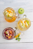 Three pitchers of lemonade with homemade. Apple, citrus, mint and ice on a white wooden background top view Royalty Free Stock Image