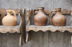 Three Pitchers. Three pottery pitchers on a wooden stand Royalty Free Stock Photos