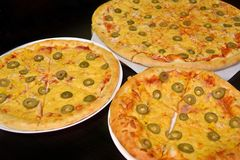 Three pizzas with cheese and olives of different sizes on a dark background stock photos