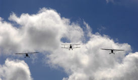 Three planes flying into cloud. Three small aircraft flying toward cloud and blue sky royalty free stock images