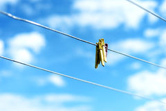 Three Plastic Clothes pegs on a Washing Line. Three brightly colored plastic clothes pegs on a  family washing line with blue sky and white summer clouds in the Royalty Free Stock Photos