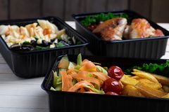 Three plastic containers with fried chicken wings and raw vegetables on rustic background, cherry tomato  and micro greens stock photography