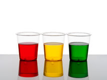 Three plastic cups of drink - red yellow and green. Stock Photo