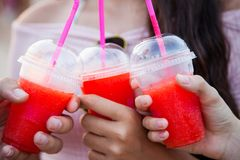 Three plastic cups with an icy red drink held by three hands stock photos