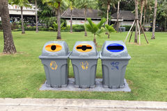 Three plastic recycle bins to separate different waste products. In park royalty free stock photo