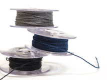 Three plastic spool of threads for sewing machine on a white bac Stock Photography