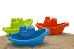 Three plastic toy boat on sand isolated. On white Stock Photo