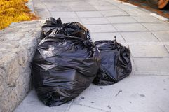 Three plastic trash bags in the street. Stock Image