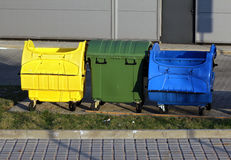 Three plastic  trash recycling bins on the street. Three plastic big trash recycling bins on the street Stock Image