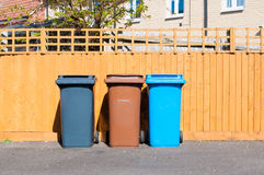 Three plastic waste bins outside a house. Along the fence Royalty Free Stock Photos