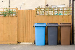 Three plastic waste bins outside a house. Along the fence Royalty Free Stock Photo