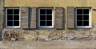 Three plastic  white  windows in the yellow plastered wall of a Royalty Free Stock Photos