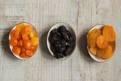 Three plates with dried fruits on wooden background: dried mandarins, prunes and dried apricots Royalty Free Stock Photo