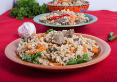 Three plates of hot delicious pilaf with garlic and parsley on r Royalty Free Stock Images