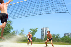 Three play beach volleyball Stock Photos