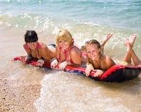 Three playing girls. Three vigorous girls playing on seashore Royalty Free Stock Image