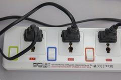Three plugs plugged into electric power bar.  Stock Photos