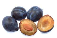 Three plums and one halved stock photos