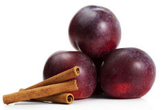 Three plums and three cinnamon sticks Stock Images