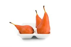 Three poached pears. Three pears poached in red wine in white dish royalty free stock photos