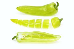 Three pointy green pepper. One half and one cut into pieces, on white background stock images