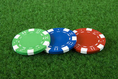 Three poker chips. Three different poker chips on green background Stock Photography