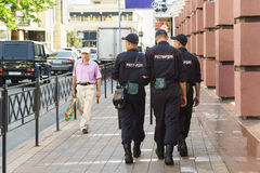 Three police patrol on a city street on a summer day. Patch royalty free stock photography